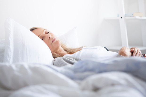 Older beautiful woman sleeping in bedroom in jeans and cardigan
